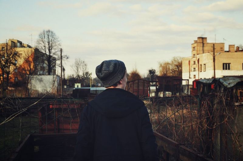 Rear view of man standing in front of buildings at town
