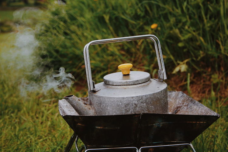 Close-up of tea kettle on field