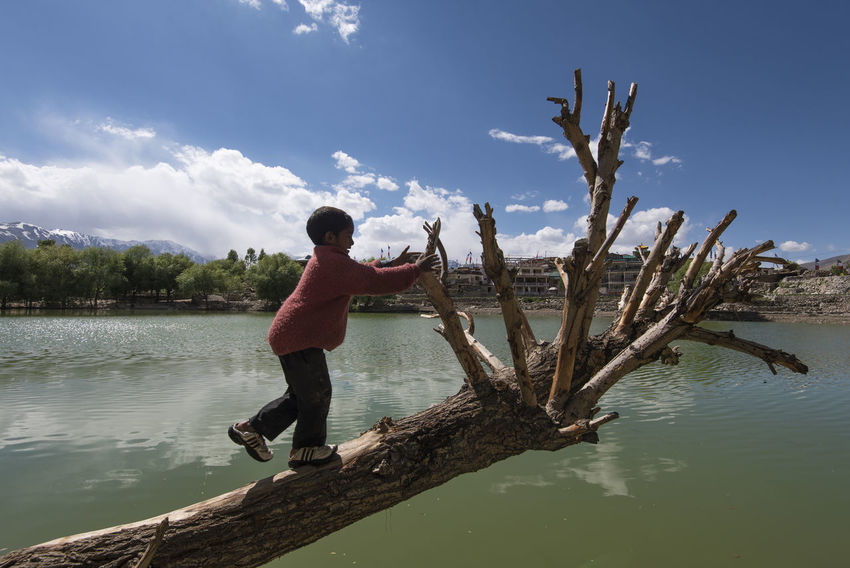 Kid playing at Nako Lake, Himachal Pradesh. Himachal Pradesh, India Nako Spiti Valley India Travel Beauty In Nature Day Full Length Lake Lake View Leisure Activity Lifestyles Nature One Person Outdoors Real People Sky Spiti Standing Tree Water Young Adult