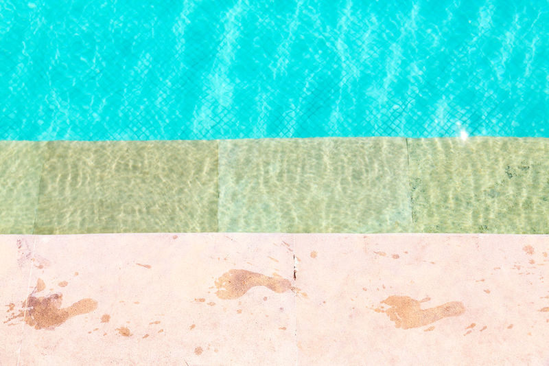 Wet foot prints on side of swimming pool Beauty In Nature Blue Close-up Day Foot Prints Nature No People Outdoors Sea Summer Sunlight Swimming Pool Swimming Pool Water Tranquility Vacations Water
