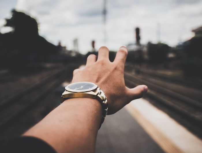 Reach Gold Body Part Day Finger Focus On Foreground Hand Human Body Part Human Finger Human Hand Lifestyles Moody One Person Outdoors Personal Perspective Rail Transportation Railroad Track Real People Time Track Transportation Watch Wristwatch