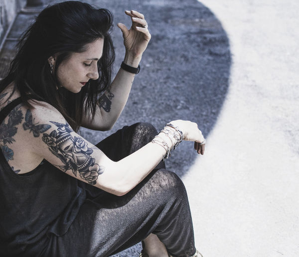 Side view of mature woman with tattoos sitting on footpath