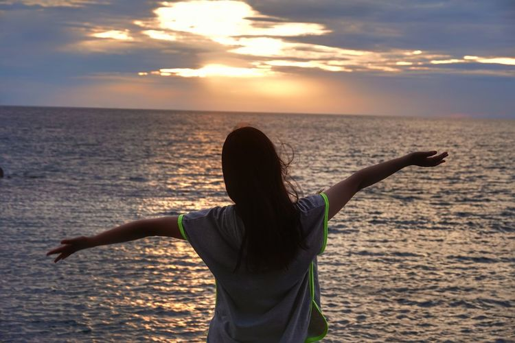 Woman standing at sea shore against sky during sunset