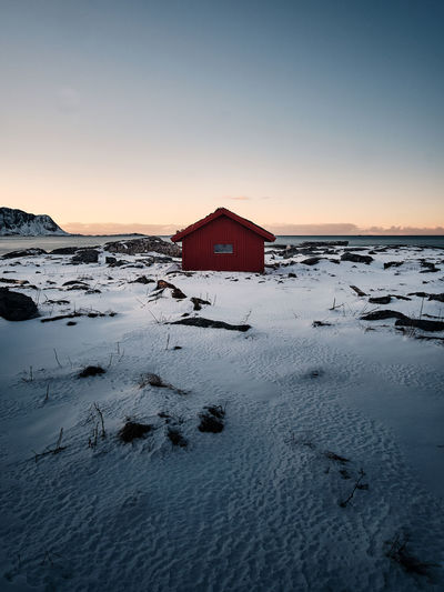 House on snow covered land by building against sky during sunset