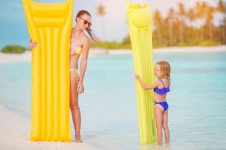 Woman standing on beach umbrella by sea