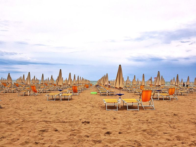 Summer At The Beach Summer Seaside Side By Side In A Row Sand Sky Outdoors Beach Sea Day Sun Umbrellas Lined Up After The Fun Closed Beach Closed Beach Umbrellas Deck Chairs Sunset Beach At Sunset in Italy