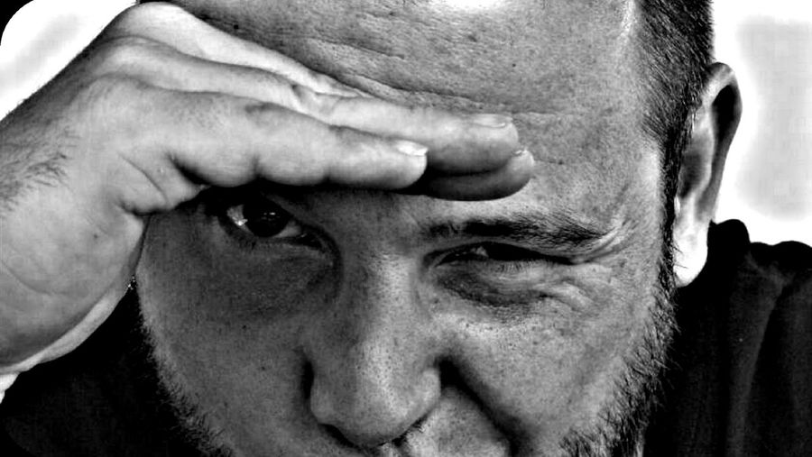 Close-up portrait of man shielding eyes