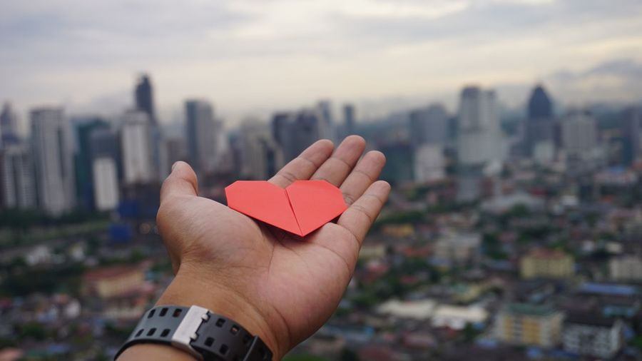 Close-up of hand holding heart shape against cityscape