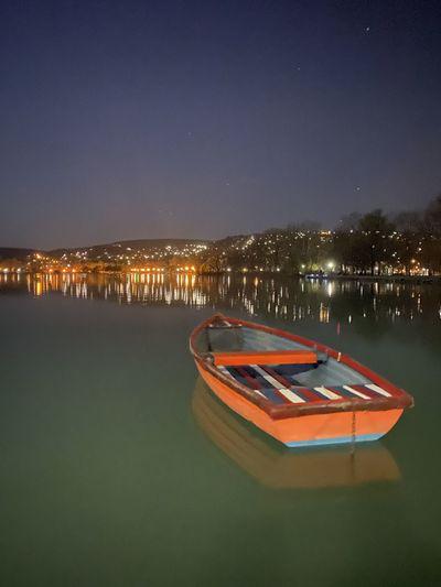 Boats moored on illuminated lake against sky at night