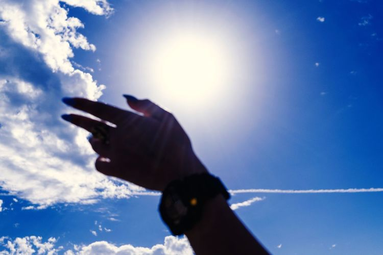 Low angle view of silhouette hand against sky
