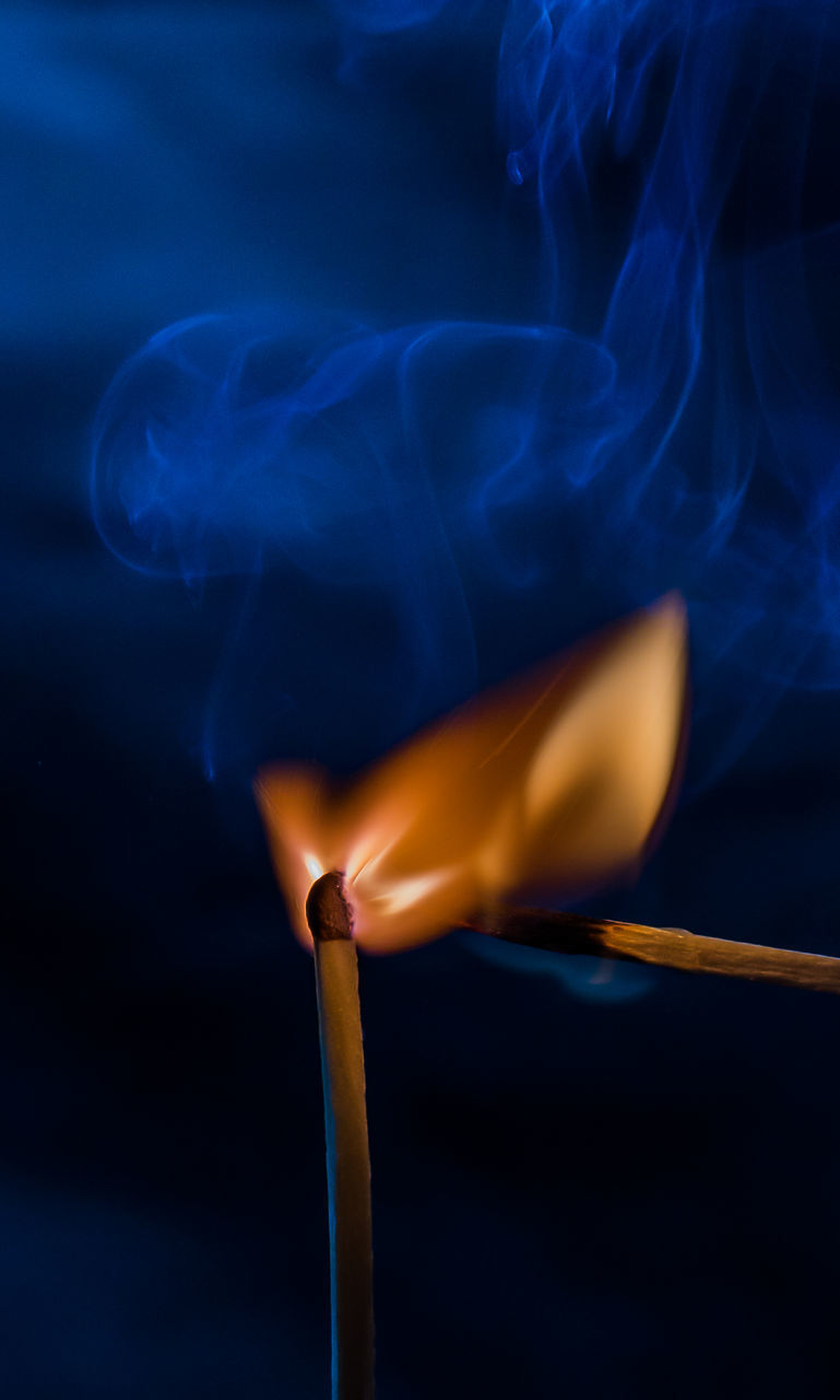 CLOSE-UP OF LIT CANDLE IN SUNLIGHT