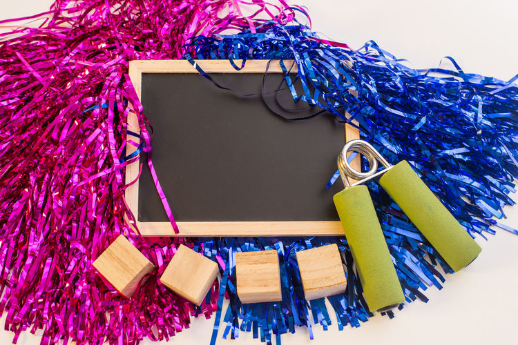 High Angle View Of Decorations With Blackboard And Blocks Over White Background