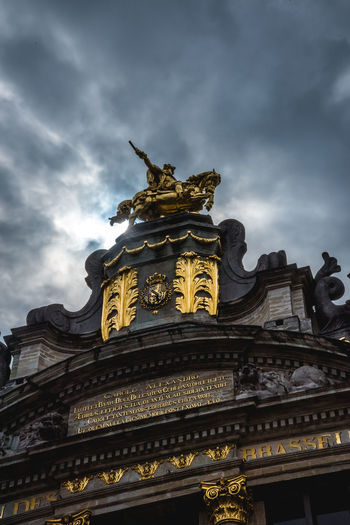 Low angle view of statue of building against cloudy sky