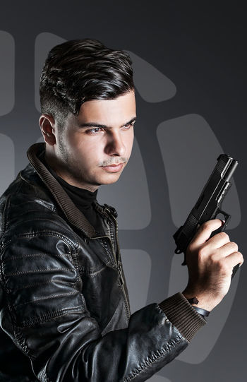 Studio photography. Portrait of a man in a leather brown jacket with a gun in his hand. As a spy from UNCLE People Watching Portraits Studio Aggression  Black Color Clothing Communication Gun Handgun Holding Indoors  Jacket Leather Leather Jacket Lifestyles Looking At Camera One Person People Portrait Real People Spy Studio Shot Weapon Young Adult Young Men