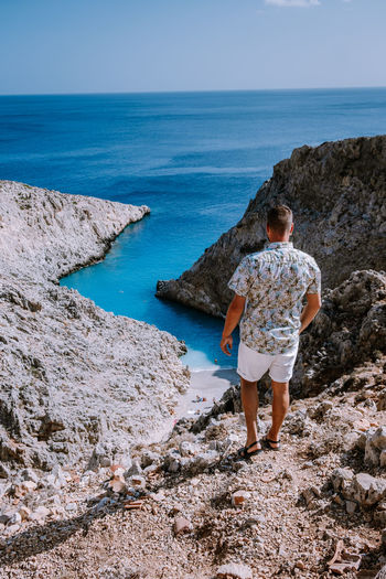 Rear view of man standing on rock while looking at sea