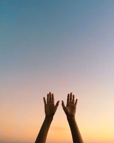 Low angle view of person hand against sky during sunset