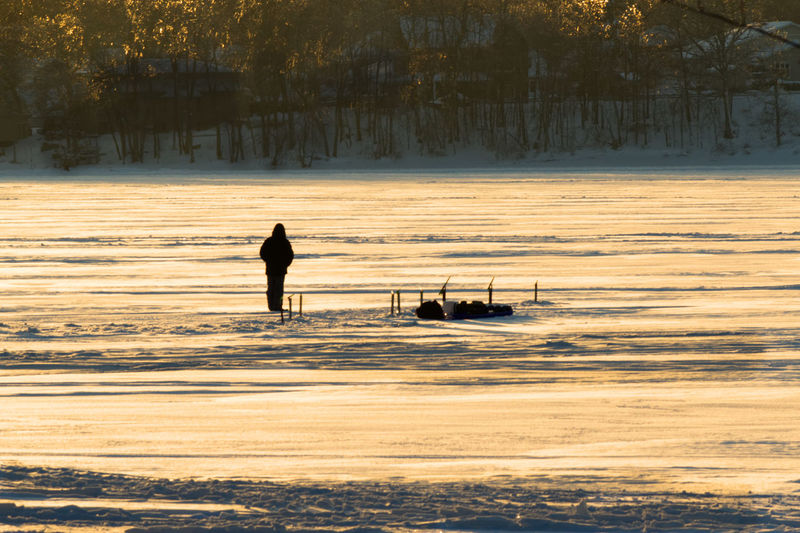 Ice fishing on the river in winter at sunset Beauty In Nature Day Full Length Leisure Activity Lifestyles Men Nature Nautical Vessel One Person Outdoors People Real People Scenics Silhouette Sky Sunset Transportation Tree Water Waterfront Wave