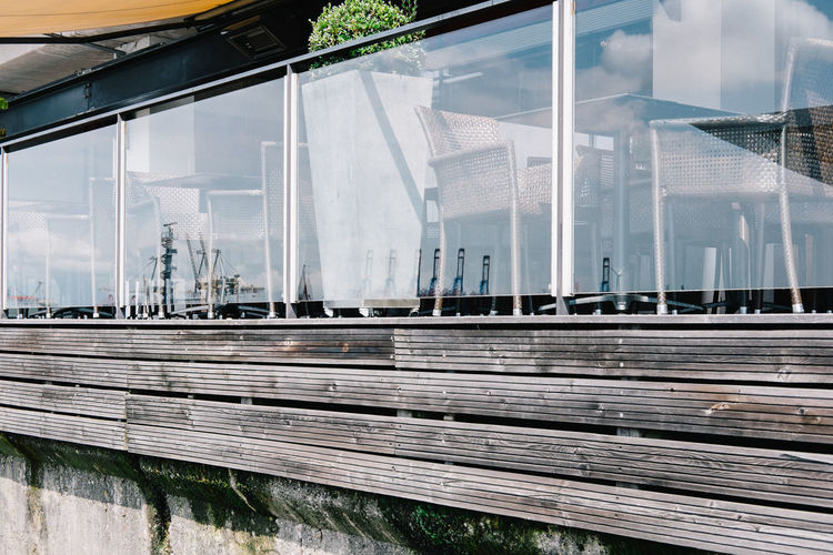 Empty chairs and tables at restaurant with crane reflections on glass railing
