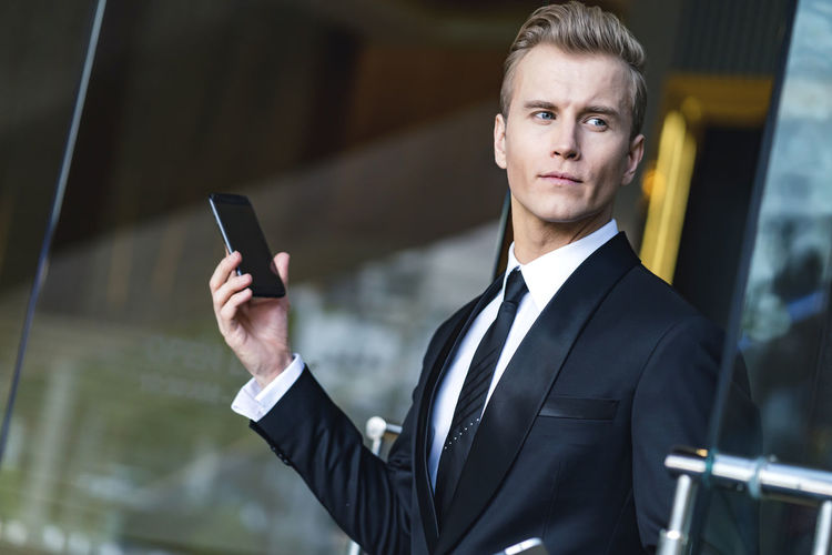 smart handsome caucasian executive officer work and contact client with smartphone office building entrance business ideas concept Work People Looking Men Modern Walking Urban Happy Construction Portrait Talking Background Lifestyle Building Airport Office Smiling Suit Arrival Smartphone Restaurant Cellphone Phone Technology Mobile Conversation Professional Smart Business Corporate Wireless Positive Transport Cheerful Communication Public Handsome Entrepreneur Confident  Contact Successful Attractive Concentrated Businessman Holding Males  Lifestyles Using Caucasian