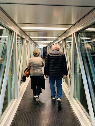 Rear view of senior couple walking on passenger boarding bridge