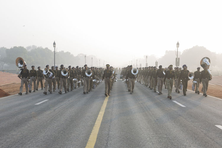 Marching band on road against sky