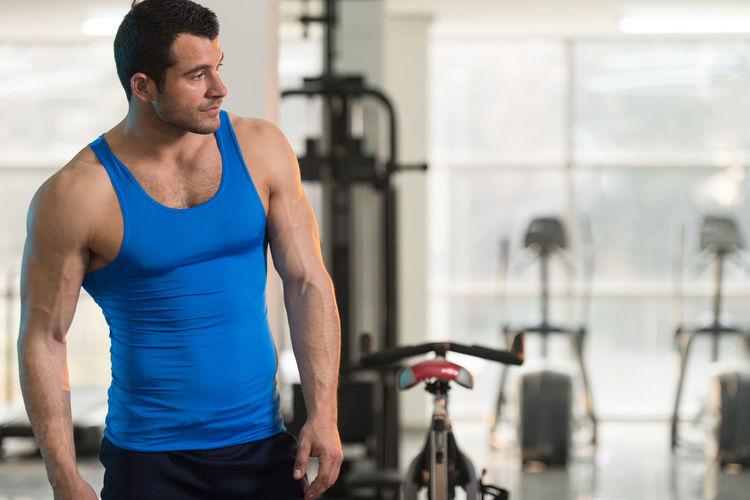 Muscular man wearing vest standing in gym