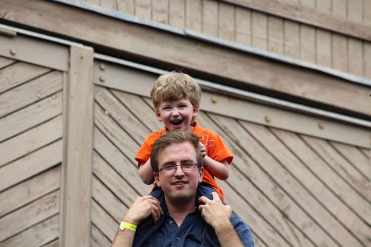 Portrait of smiling father carrying son on shoulder against wall