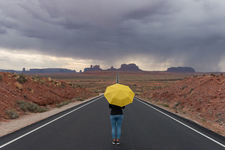 Woman With Umbrella Standing On Road Leading Towards Monument Valley