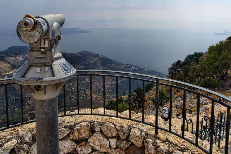Coin-operated binoculars at observation point on mountain by sea