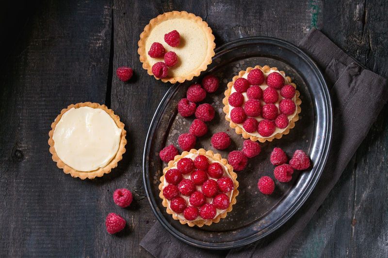Unfinished and ready to eat tartlets with custard and fresh ripe raspberries, served on vintage metal tray with baking forms and textile napkin over old wooden table. Dark rustic style. Flat lay Breakfast Shortbread Tart Tartlette Bake Baked Pastry Item Bakery Berry Fruit Custard Dark Background Dessert Flat Lay Food Food And Drink Fruit Group Lemon Curd Raspberry Red Rustic Style Shortbread Tartlet Sweet Sweet Food Tart - Dessert Top View