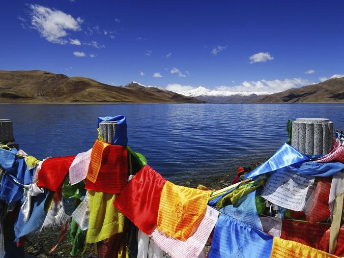 colorful view with flags at blue sea Beauty In Nature Blue Cloud - Sky Colorful Idyllic Lake Lake View Landscape Lifestyles Mountain Nature Outdoors Sky Tibet Tibet Flag Tranquil Scene Tranquility Water