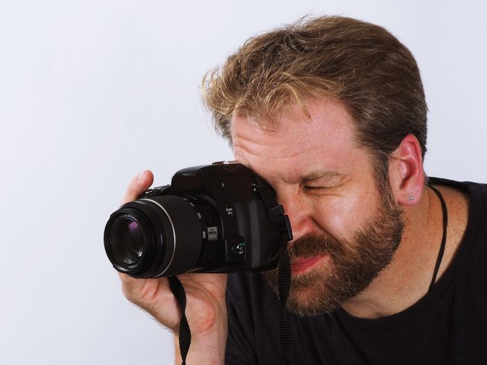 Close-up of man photographing against white background