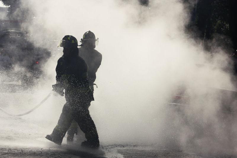 Silhouette firemen on street