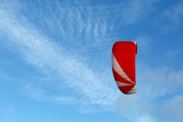 Low angle view of red kite parachute against blue sky