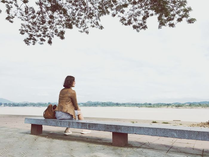 Woman looking at lake while sitting on bench against sky