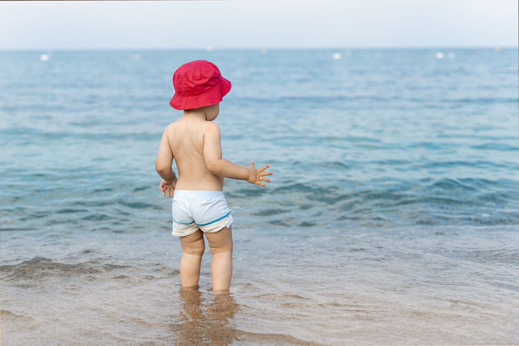 Rear view of shirtless boy standing on beach