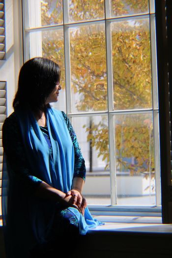 Woman looking through window while sitting at home
