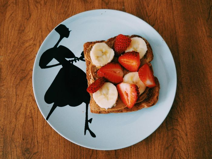 Directly above shot of sliced strawberries and bananas on breads in plate