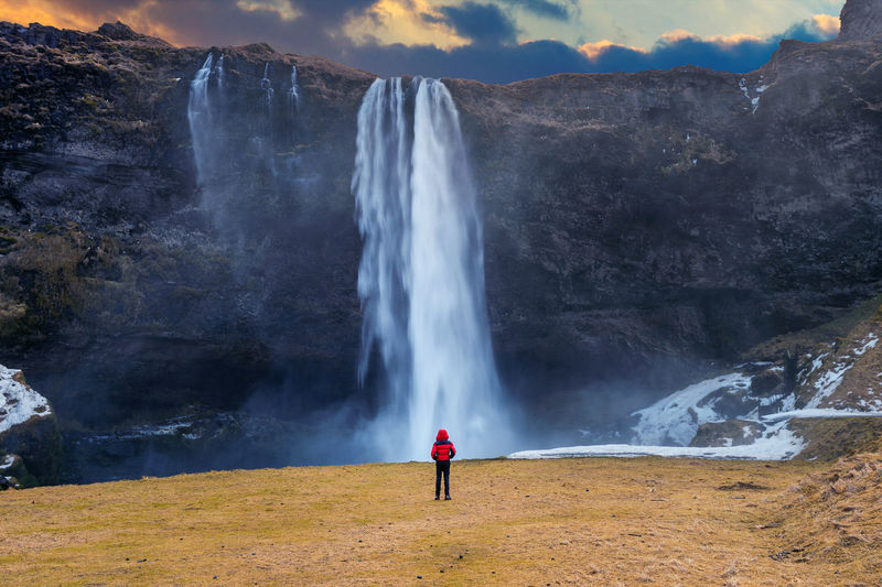 Seljalandsfoss waterfall in Iceland. Guy in red jacket looks at Seljalandsfoss waterfall. Beauty In Nature Environment Flowing Water Leisure Activity Lifestyles Long Exposure Motion Mountain Nature Non-urban Scene One Person Outdoors Power In Nature Real People Scenics - Nature Standing Tourism Travel Travel Destinations Water Waterfall