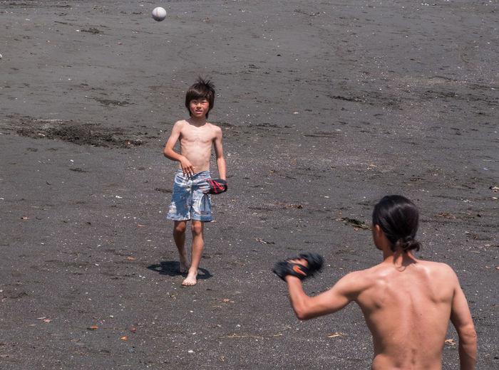 Full length of shirtless boy standing on beach