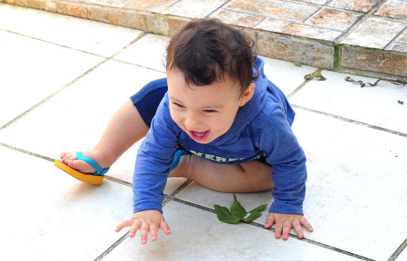 High Angle View Of Cheerful Baby Boy Sitting On Tiled Floor