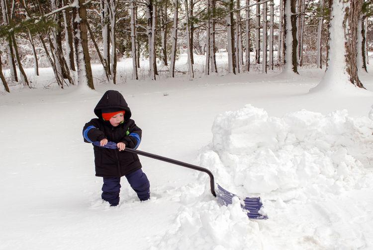 Boy Digging Snow During Winter