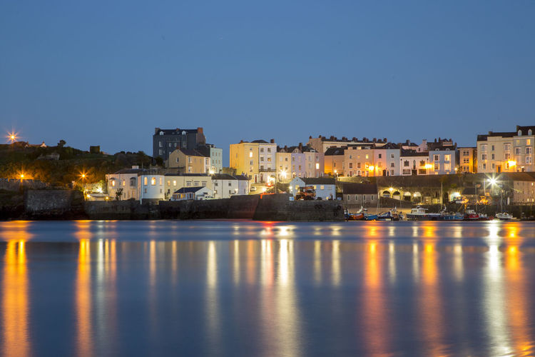 Illuminated buildings by sea against clear sky at night