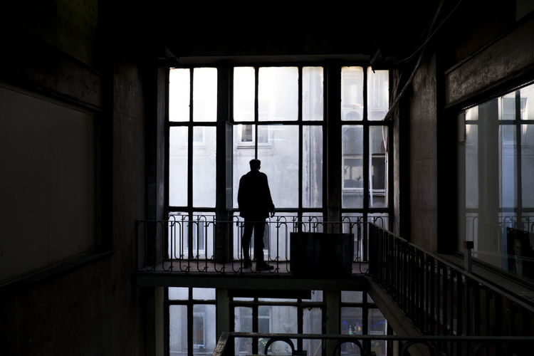 Silhouette Man Standing By Window