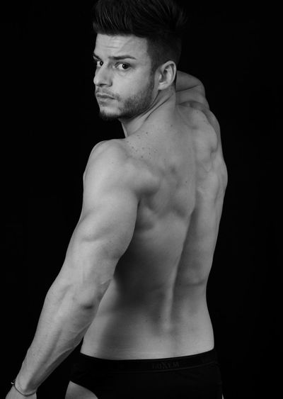 Portrait of shirtless muscular man standing against black background