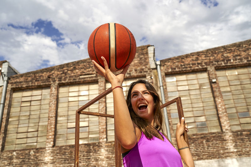 Young woman with ball in hair against sky