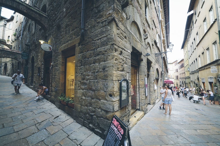 Wide angle view of the streets of the medieval city of Volterra, Tuscany, Italy. Ancient Architecture Building Exterior Built Structure City Cobblestone Day Historic Italy Medieval Men Old Outdoors People Real People Stone Street Travel Tuscany Volterra Walking Women EyeEmNewHere