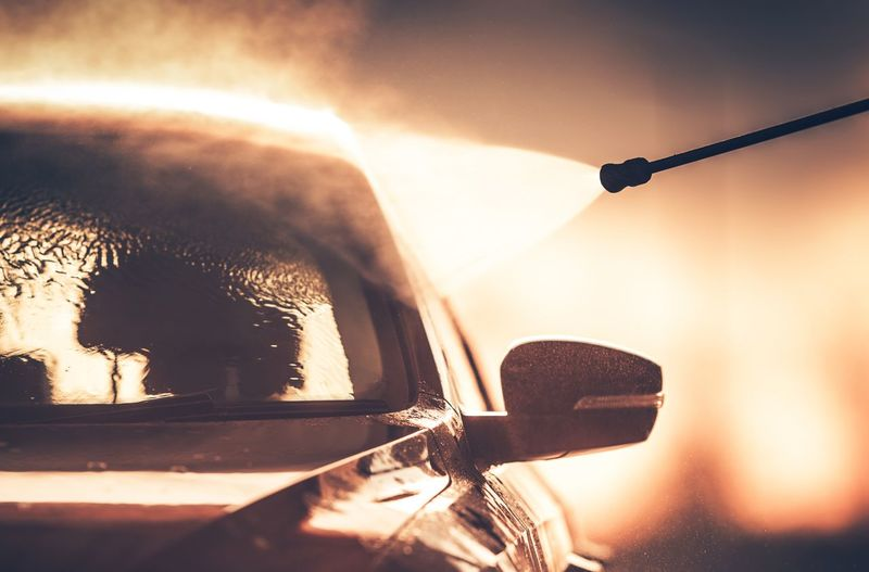 Silhouette Pipe Spraying Water On Car During Sunset