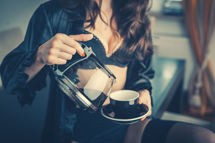 Woman in dressing gown in the morning pouring herself a coffee for breakfast Breakfast Close-up Coffee Cup Dressing Gown Drinking Food And Drink Holding Human Hand One Person People Real People Sensual_woman Torso Women