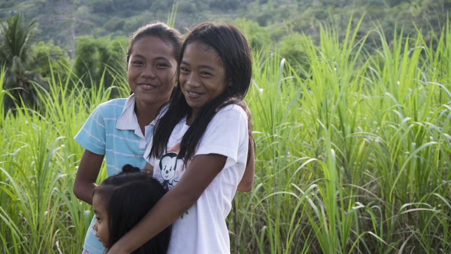 Mother and daughter standing on grassy field